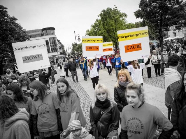 kilkadziesiąt młodych osób na ulicy z tabliczkami: niepełnosprawny mówi, kocha, czuje